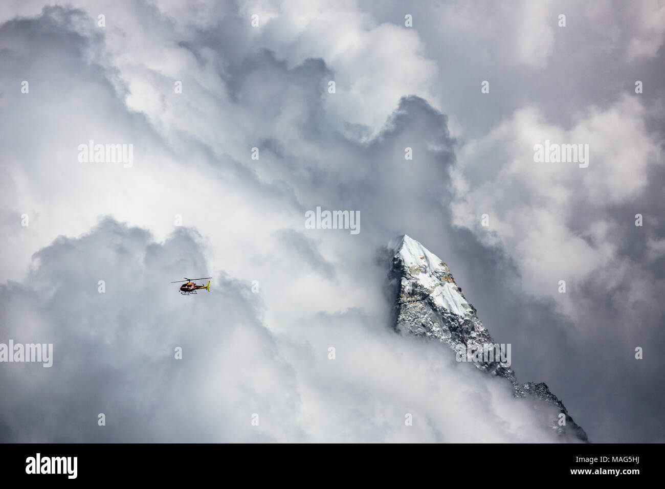 A Eurocopter flying in dangerous conditions at 15,000ft in the clouds but still below mountain peaks on its way to base camp of Mt. Everest. Nepal - Stock Image