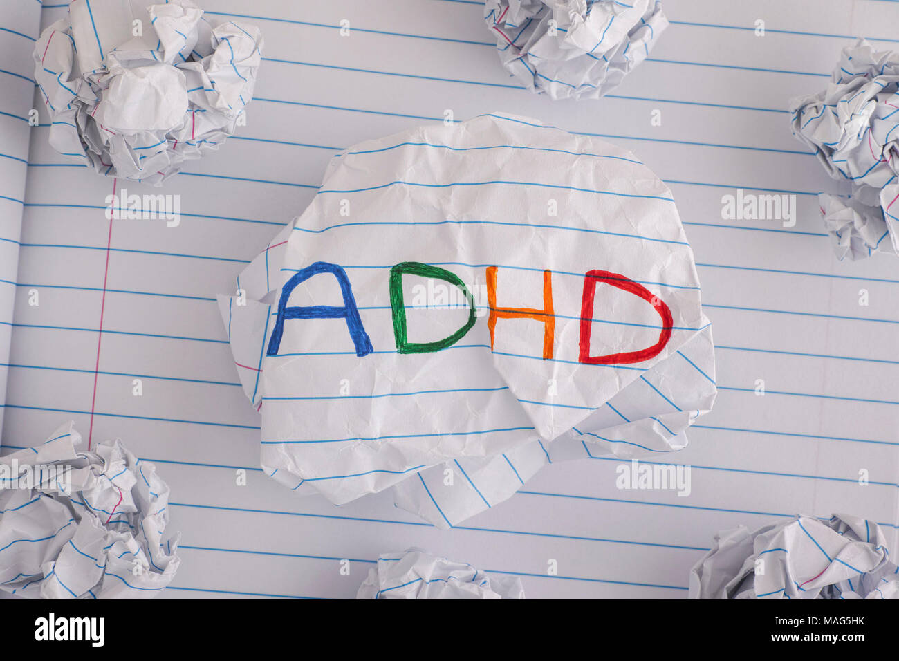 ADHD. Abbreviation ADHD on crumpled paper ball. Close up. ADHD is Attention deficit hyperactivity disorder. - Stock Image