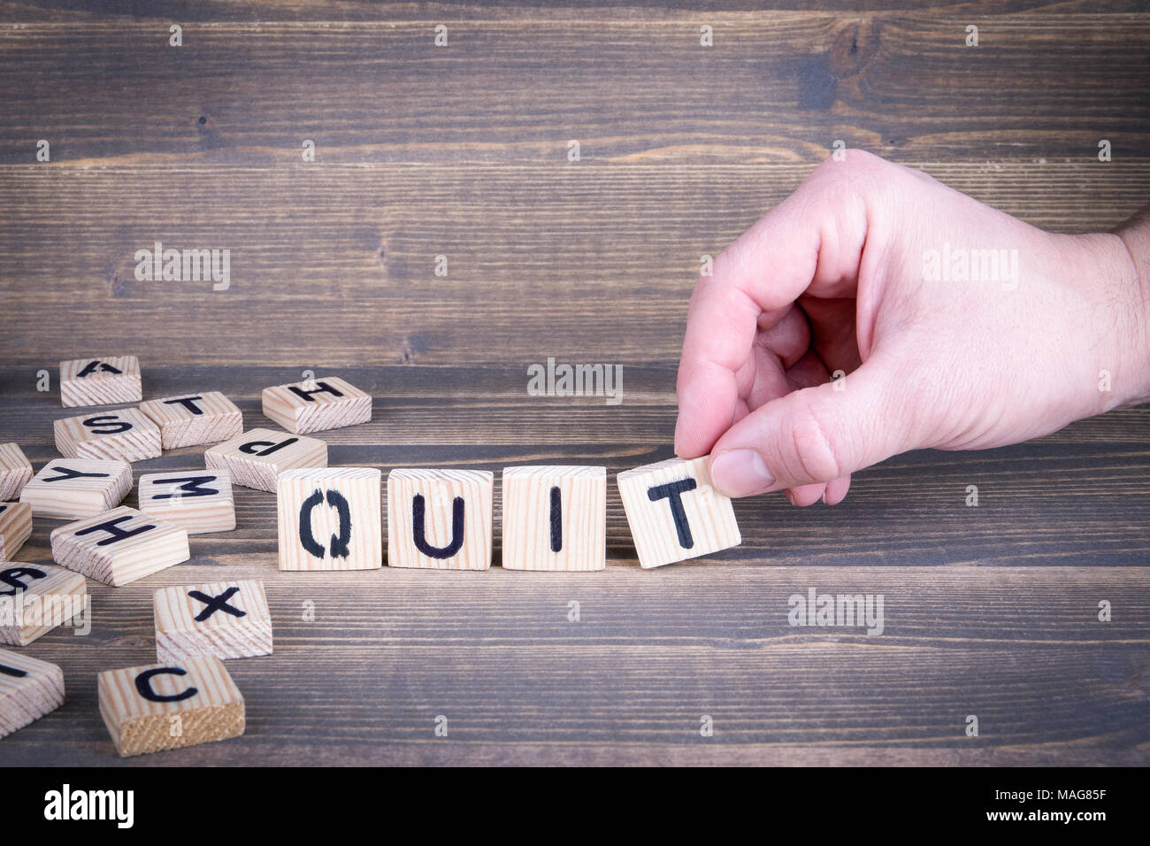 Quit. Wooden letters on the office desk - Stock Image