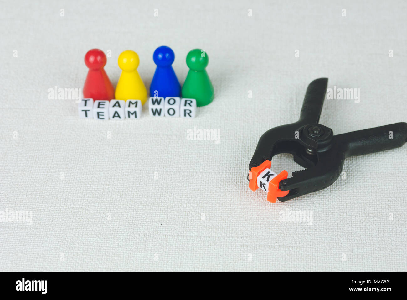 Team work concept - Figures in the line and an clamp tool as symbol for a working labor team collaboration - Stock Image