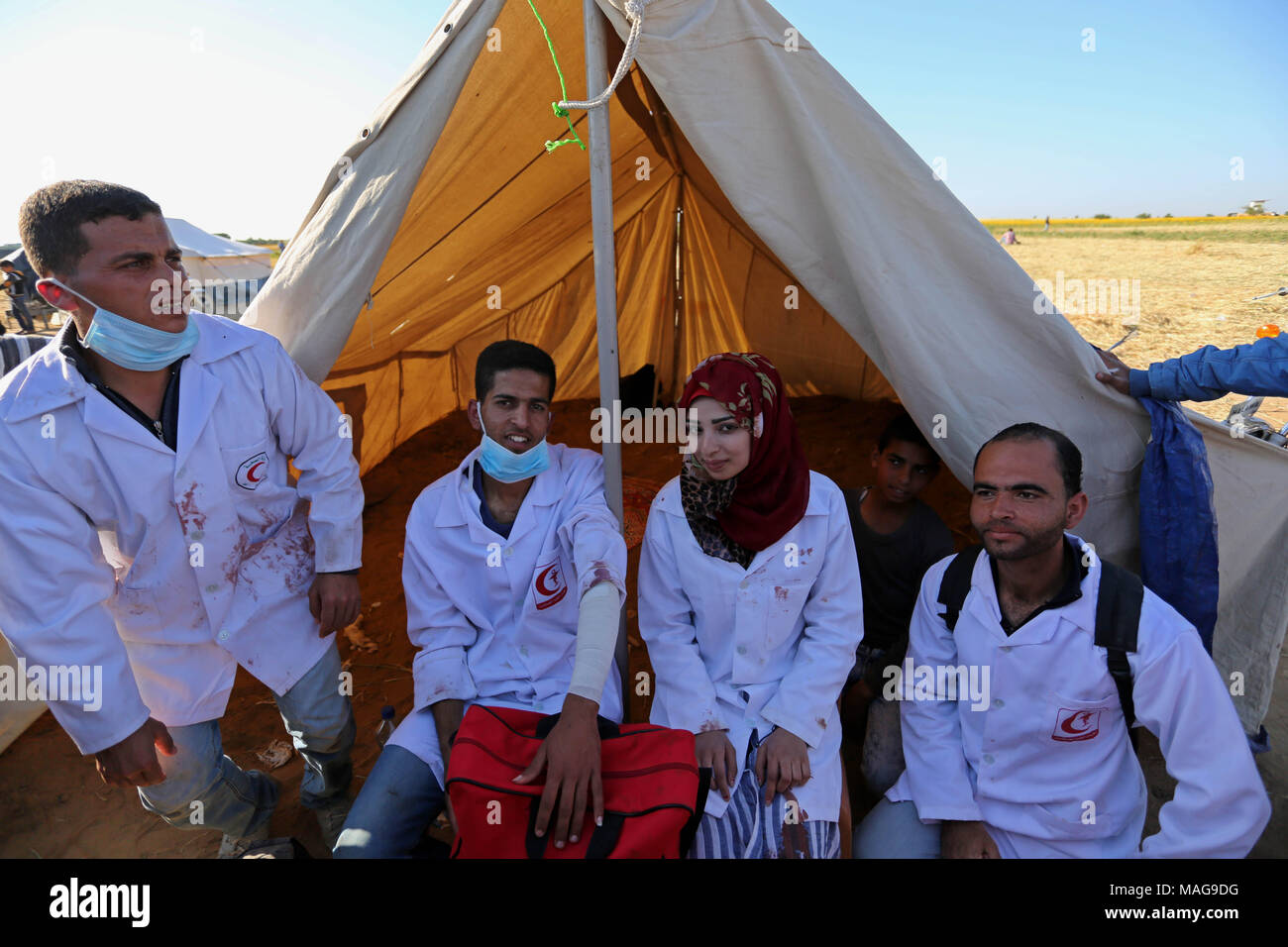 Khan Younis, Gaza Strip, Palestinian Territory. 1st Apr, 2018. Palestinian medical Razan al-Najjar and her comrades sit next to medical tent during clashes with Israeli security forces in a protest, at the Israel-Gaza border, demanding the right to return to their homeland, in Khan Younis in the southern Gaza strip on April 1, 2018 Credit: Ashraf Amra/APA Images/ZUMA Wire/Alamy Live News - Stock Image