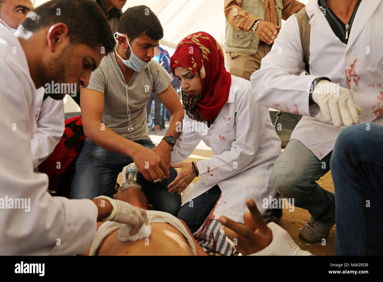 Khan Younis, Gaza Strip, Palestinian Territory. 1st Apr, 2018. Palestinian medical Razan al-Najjar helps an injured Palestinian man at an emergency medical tent during clashes with Israeli security forces in a protest, at the Israel-Gaza border, demanding the right to return to their homeland, in Khan Younis in the southern Gaza strip on April 1, 2018 Credit: Ashraf Amra/APA Images/ZUMA Wire/Alamy Live News - Stock Image