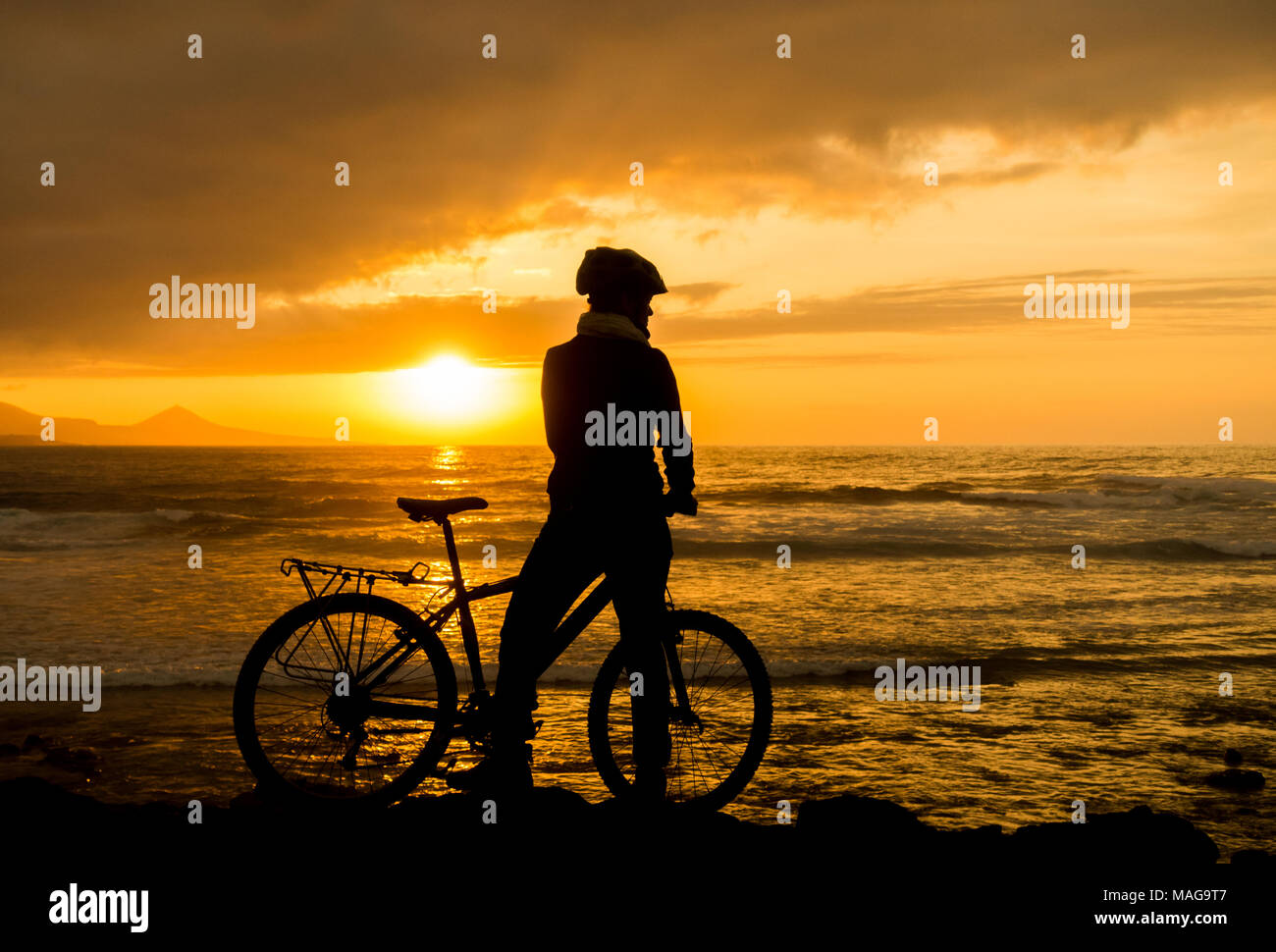 female mountain biker at sunset on the north coast of Gran Canaria, Canary Islands, Spain - Stock Image