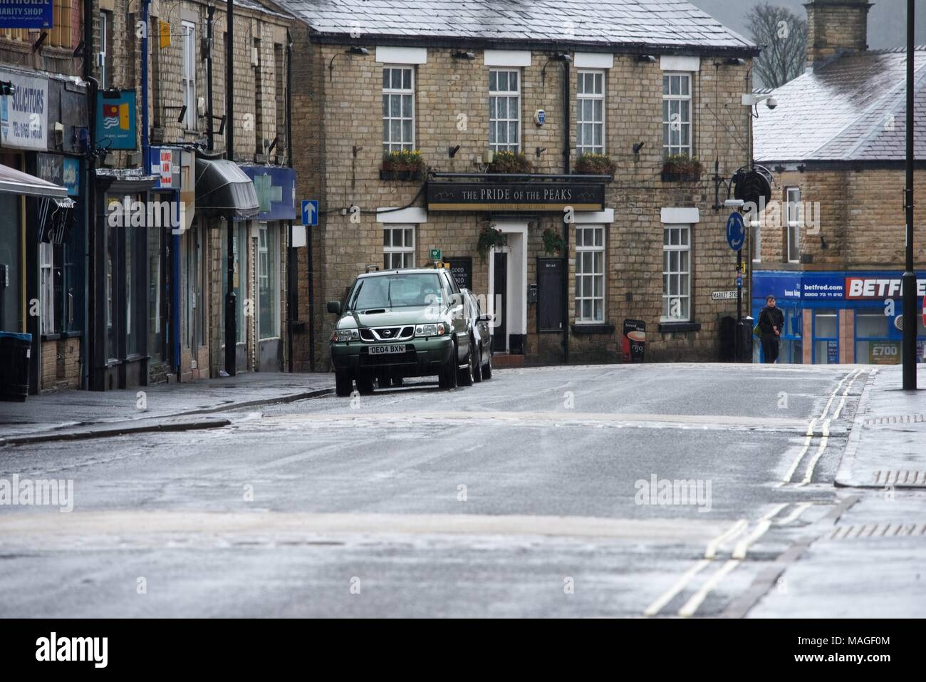 New Mills. High Peak. Derbyshire. 2nd April 2018. UK Weather: A wet and a solitary figure in the main street in New Mills on Easter Monday morning. Credit: John Fryer/Alamy Live News - Stock Image