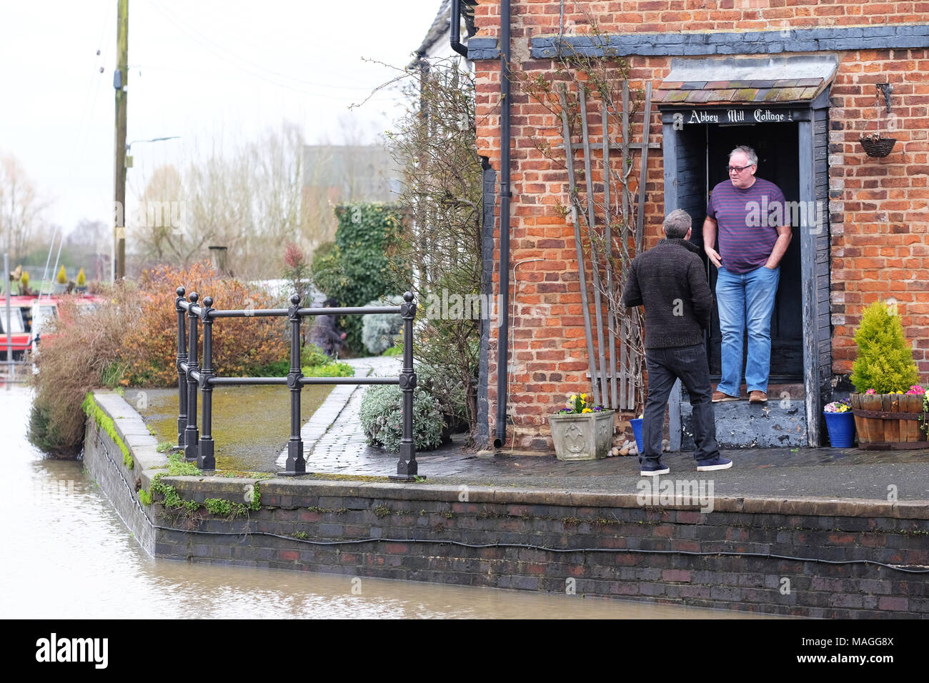 Tewkesbury, Gloucestershire - Bank Holiday Monday 2nd April 2018 - UK Weather: Local residents watch as water levels rise outside their riverside homes in Tewkesbury - the flooding at the confluence of the River Severn and the River Avon has already covered the lane beside the rivers - Photo Steven May  / Alamy Live News Stock Photo