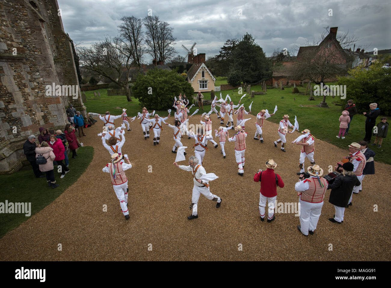 Church Yard Thaxted, Essex. 2nd Apr, 2018. Traditional Easter Monday Morris Dancing. Under louring skies the Thaxted Morris Men ( red and white stripes) dance with Devil's Dyke Morris Men from Newmarket area ( white shirts ) on Easter Monday in front of the ancient Alms Houses and John Webb's Windmill in the Church Yard Thaxted, Essex. 2 April 2018 Credit: BRIAN HARRIS/Alamy Live News - Stock Image
