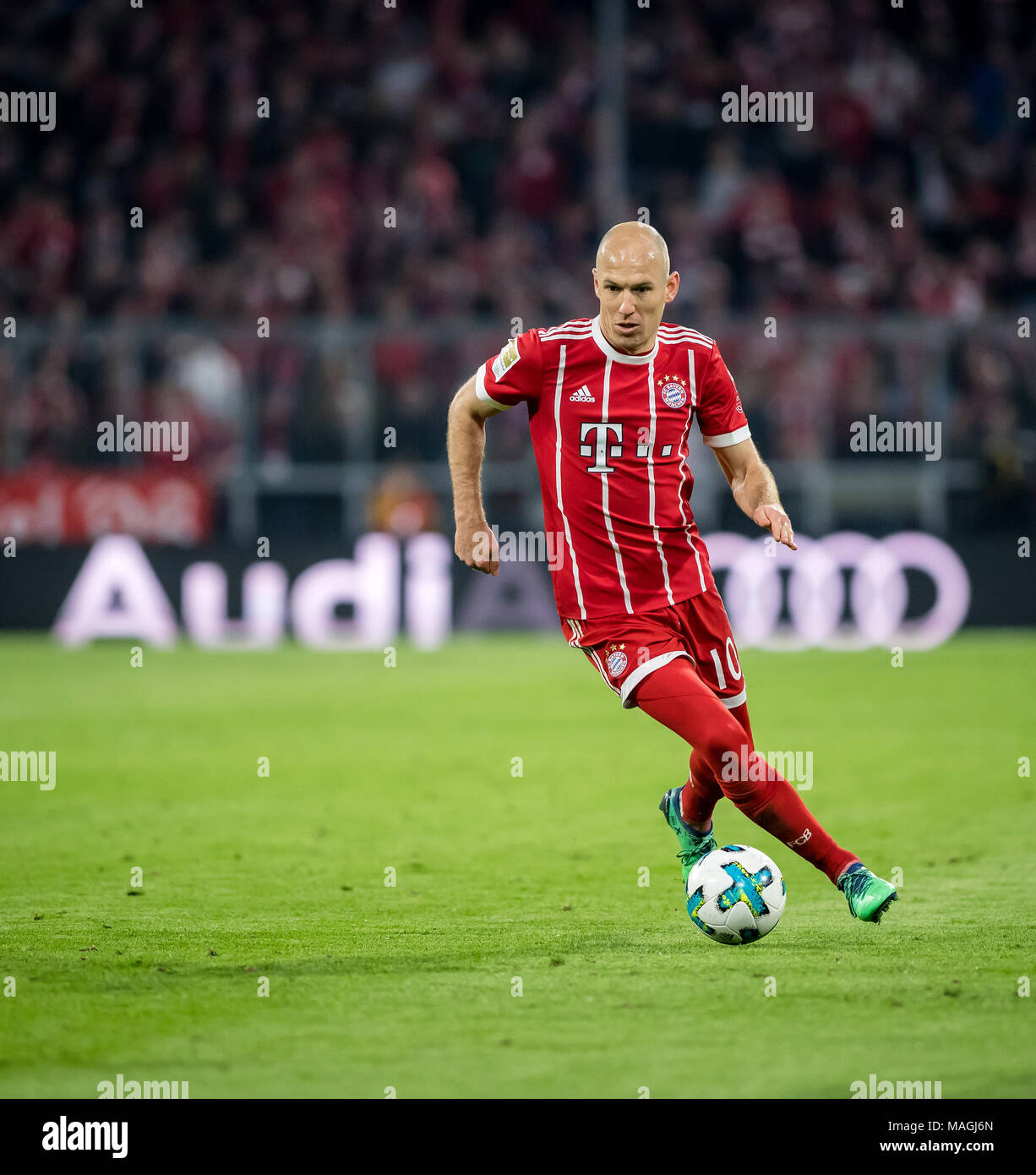 31 March 2018: Germany, Munich, Allianz Arena: Soccer 1. Bundesliga: FC Bayern Muenchen vs Borussia Dortmund: Muenchen's Arjen Robben after the ball in front of an Audi advertising board. - NO WIRE SERVICE- Photo: Thomas Eisenhuth/dpa-Zentralbild/ZB - Stock Image