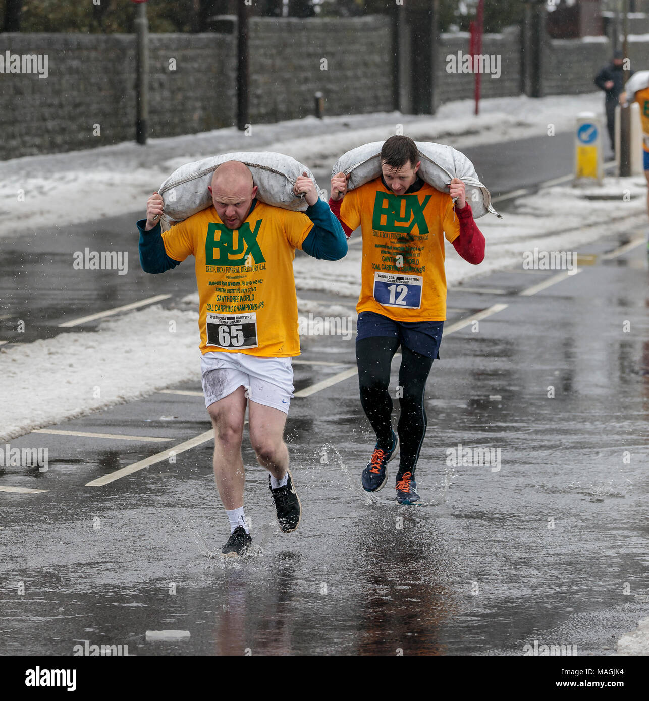 Gawthorpe, West Yorkshire, UK. 2nd April 2018. Leading runners in the first of two men's races. The World Coal Carrying Championships take place every year on Easter Monday, when competitors, carrying sacks of coal, race over a 1012 m uphill course through the former mining village near Wakefield. Male competitors carry 50kg sacks and females 20kg. Women's winner was Danielle Sidebottom, Men's winner was Andrew Corrigan. © Ian Wray/Alamy live news - Stock Image