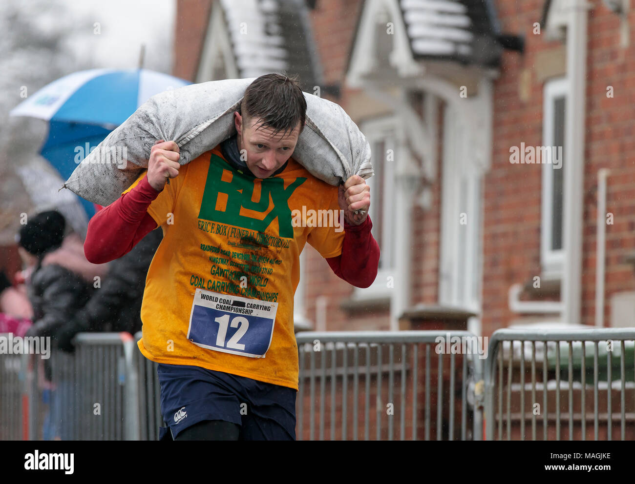 Gawthorpe, West Yorkshire, UK. 2nd April 2018. Winner of the first of two men's races nears the finish line. The World Coal Carrying Championships take place every year on Easter Monday, when competitors, carrying sacks of coal, race over a 1012 m uphill course through the former mining village near Wakefield. Male competitors carry 50kg sacks and females 20kg. Women's winner was Danielle Sidebottom, Men's winner was Andrew Corrigan. © Ian Wray/Alamy live news - Stock Image