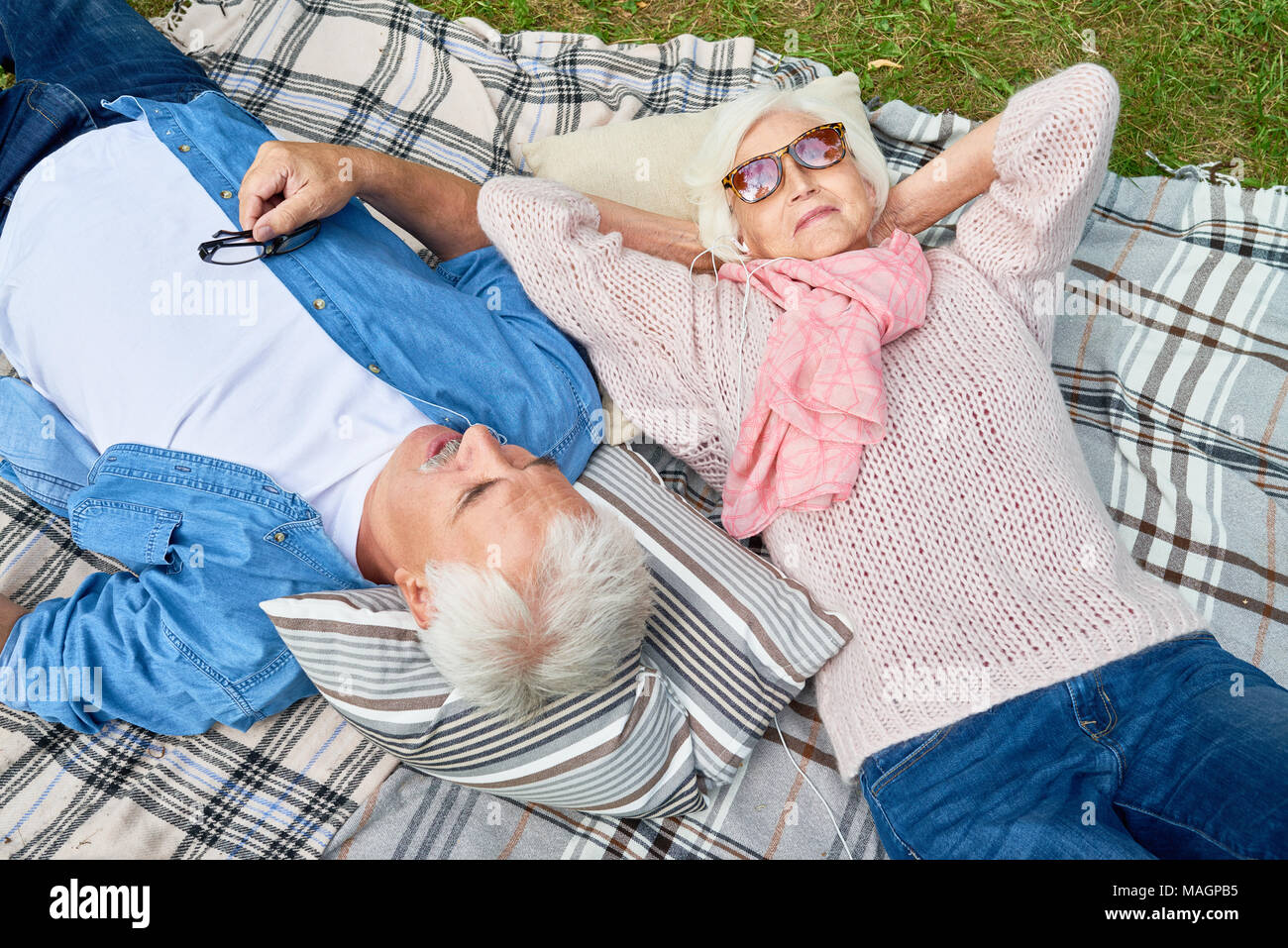 Senior Woman Listening to Music at Picnic - Stock Image