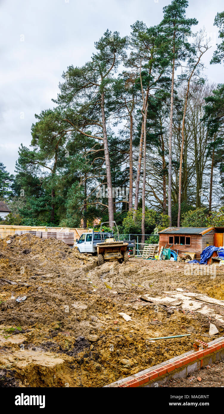 Dumper and white van on a muddy churned up residential construction site in Surrey, southeast England in wet, bad weather - Stock Image