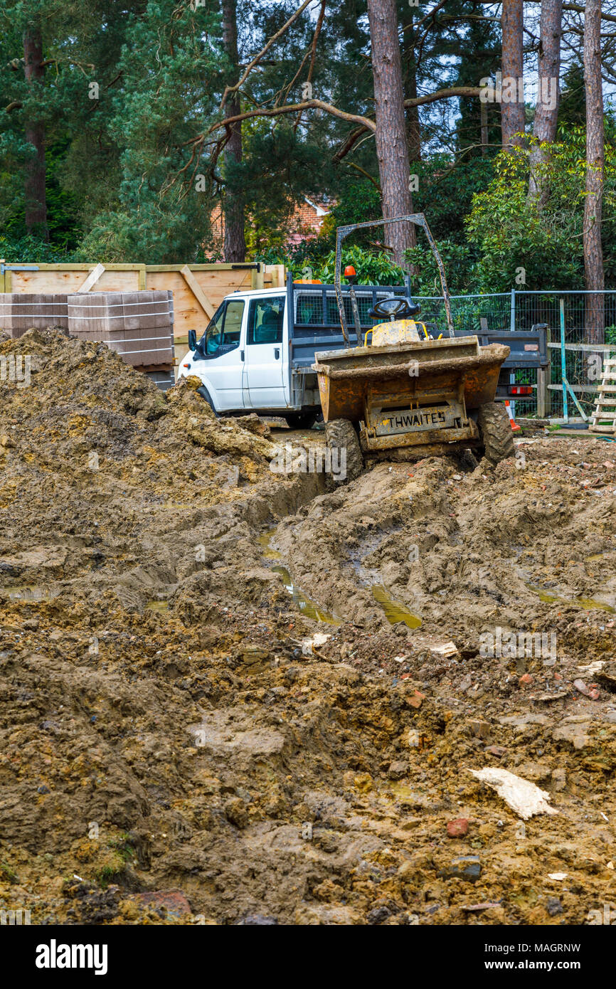 Dumper and white van on a muddy churned up residential construction site in Surrey, southeast England after wet, bad weather - Stock Image