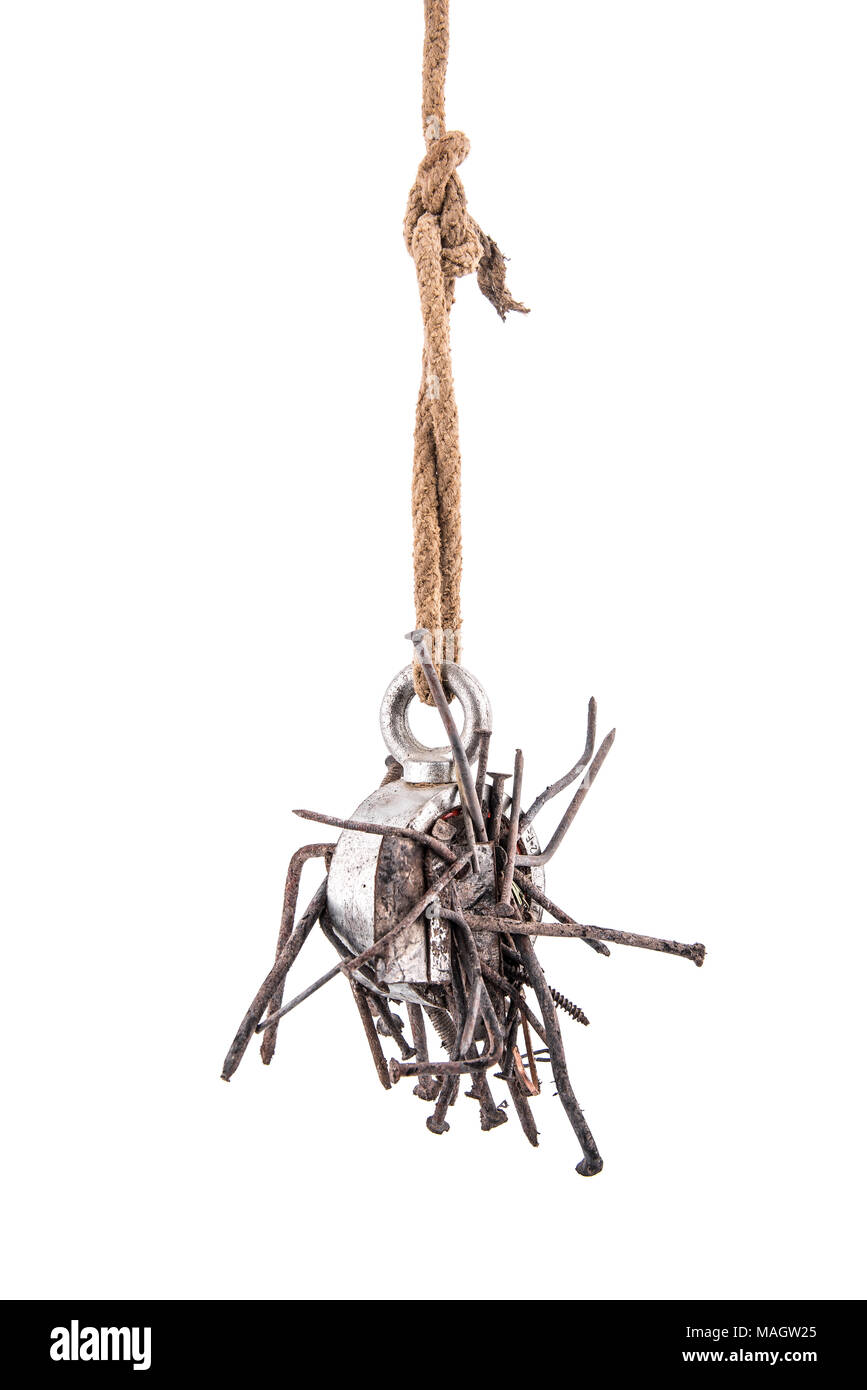 Two-way steel search magnet with rusty nails hanging on rope, isolated on white background - Stock Image