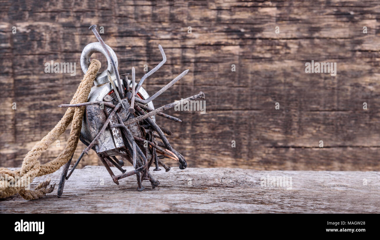 Two-way steel search magnet with rusty nails and old rope on wooden table, text place - Stock Image