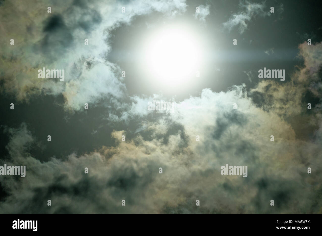 Sun dramatically shining through fluffy clouds. - Stock Image