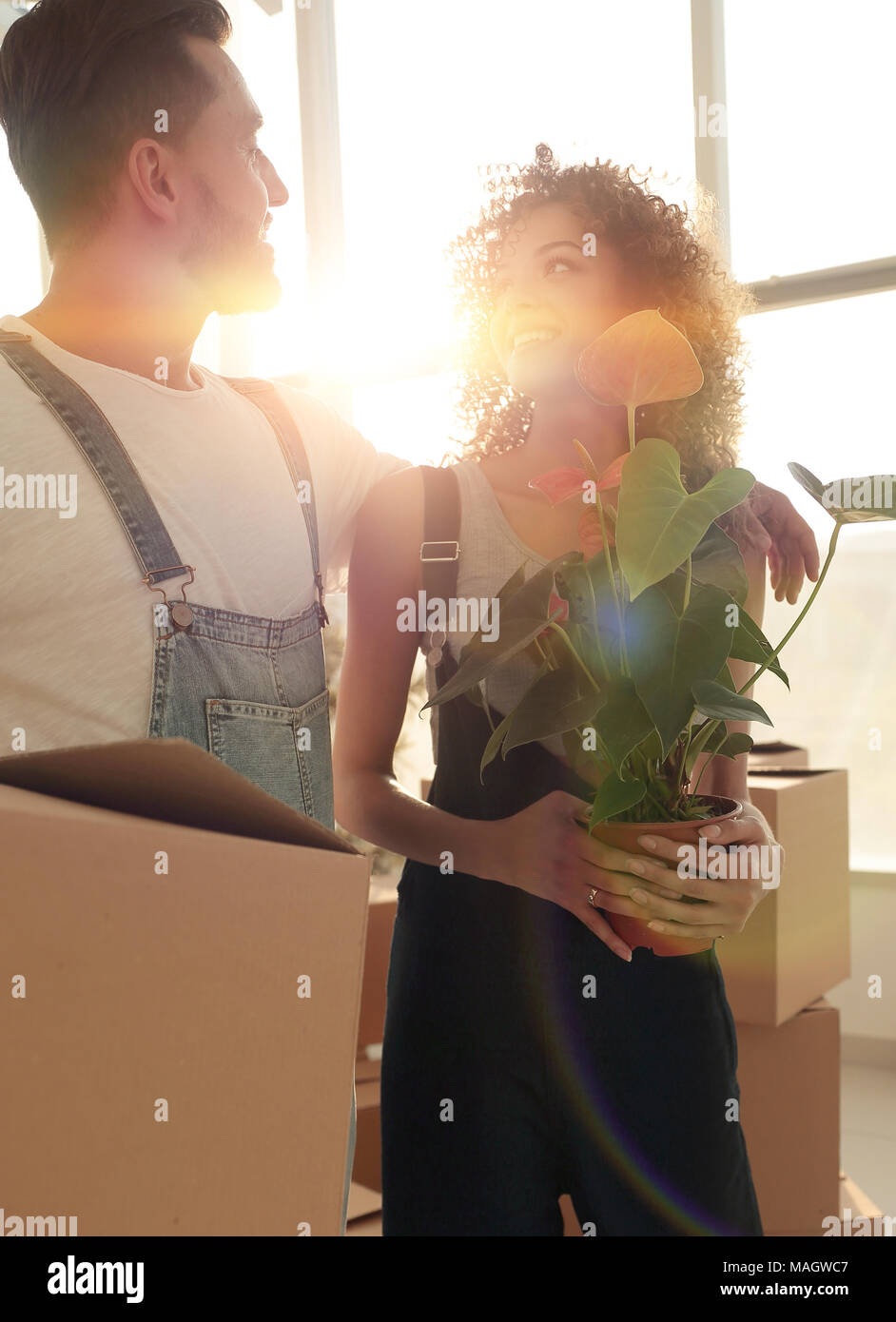 Close-up of a beautiful young couple is carrying things into a n Stock Photo