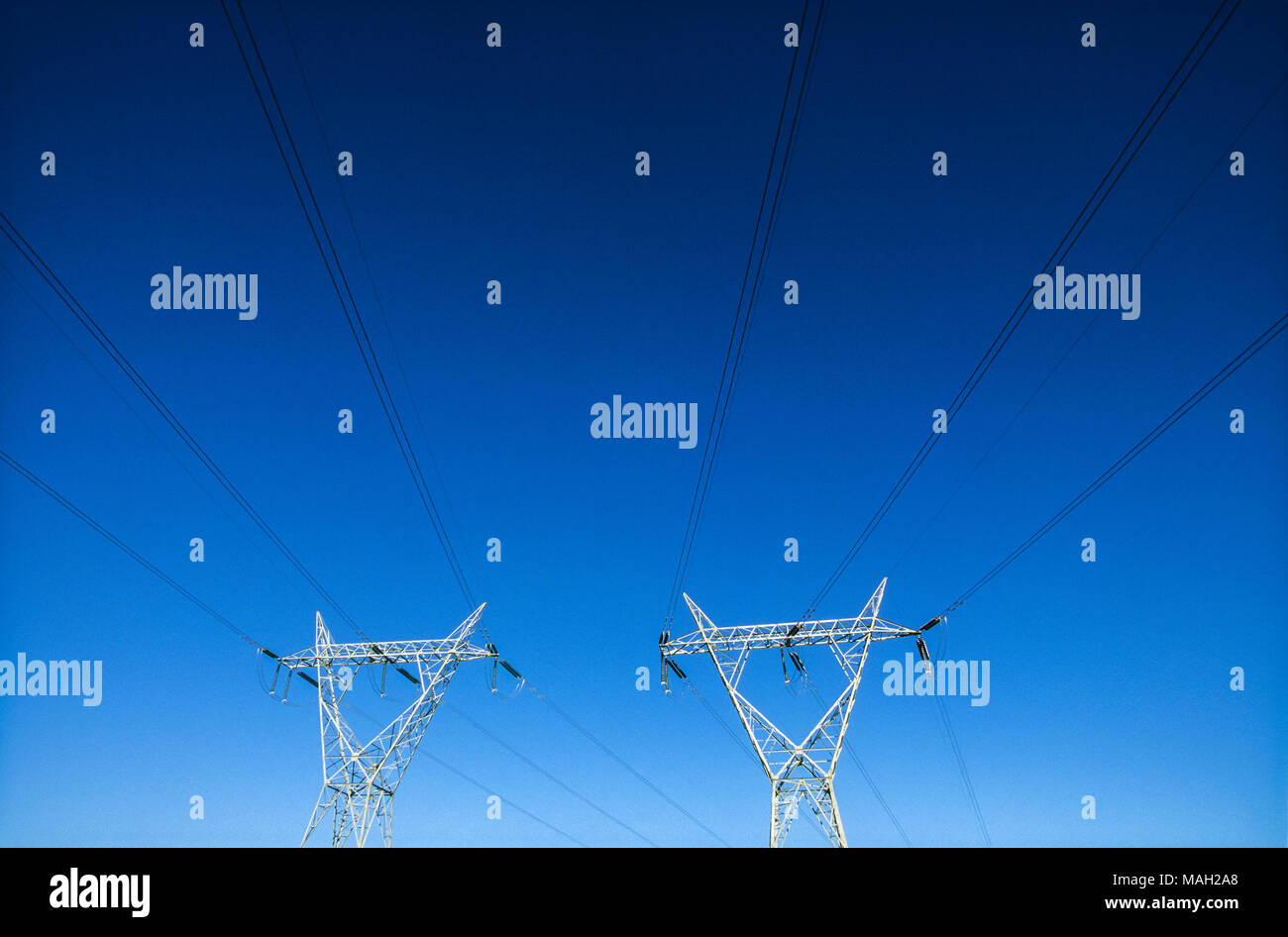 electricity transmission pylons in blue sky - Stock Image