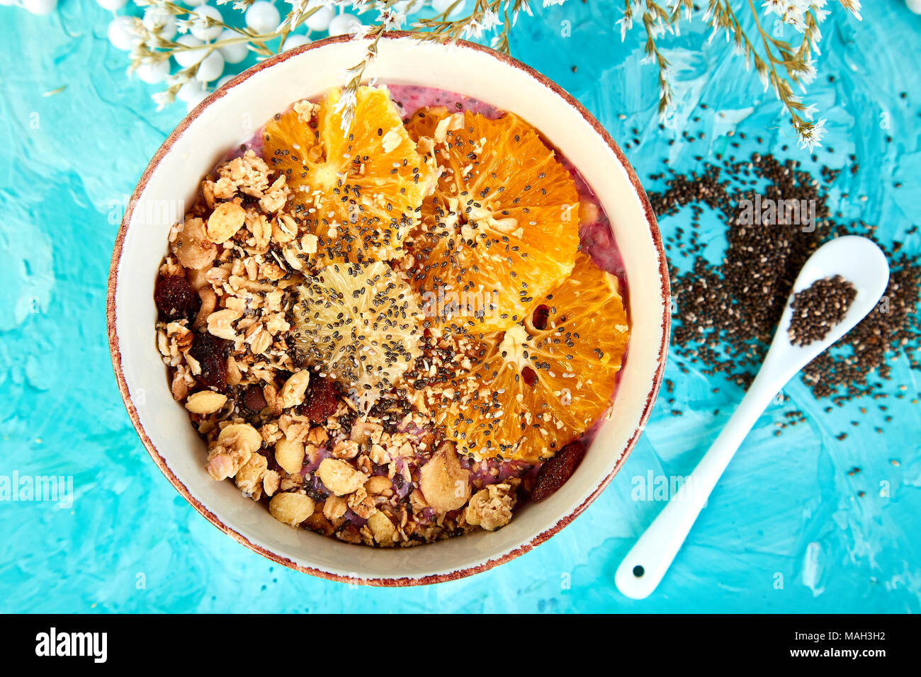 Detox and healthy superfoods breakfast bowl concept. Vegan coconut milk chia seeds pudding with granola and citrus. top view, flat lay. - Stock Image