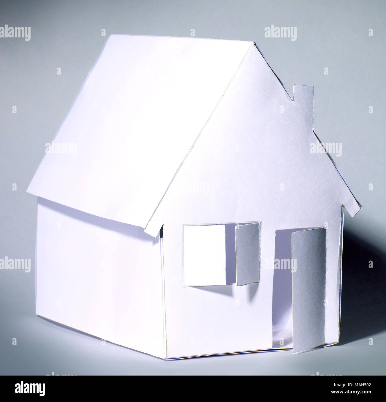 paper house with open door.isolated on grey - Stock Image