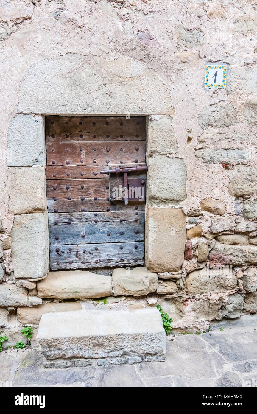 old wooden door in the village of El Mallo, Garrotxa, Catalonia, Spain - Stock Image
