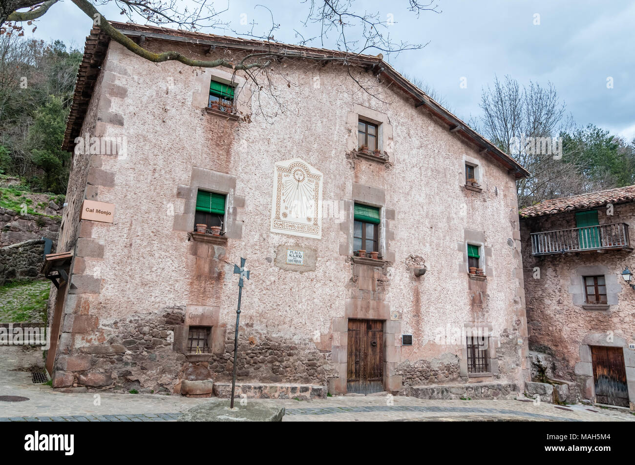 facade of an old house in the main square, sundial, Sant Privat, Garrotxa, Catalonia, Spain - Stock Image
