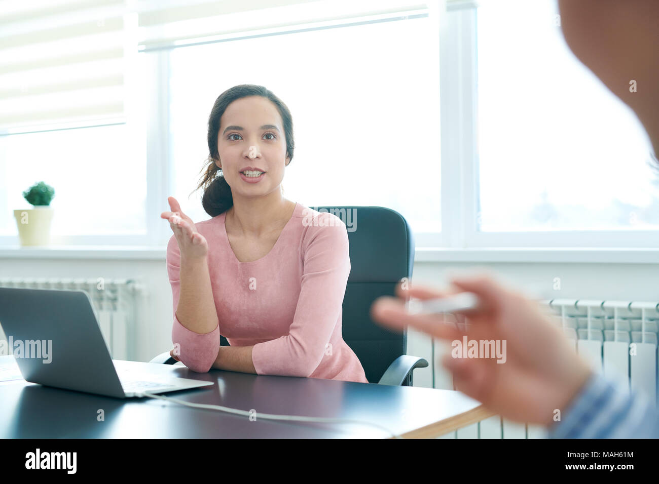 Enthusiastic business lady discussing agenda with colleague - Stock Image