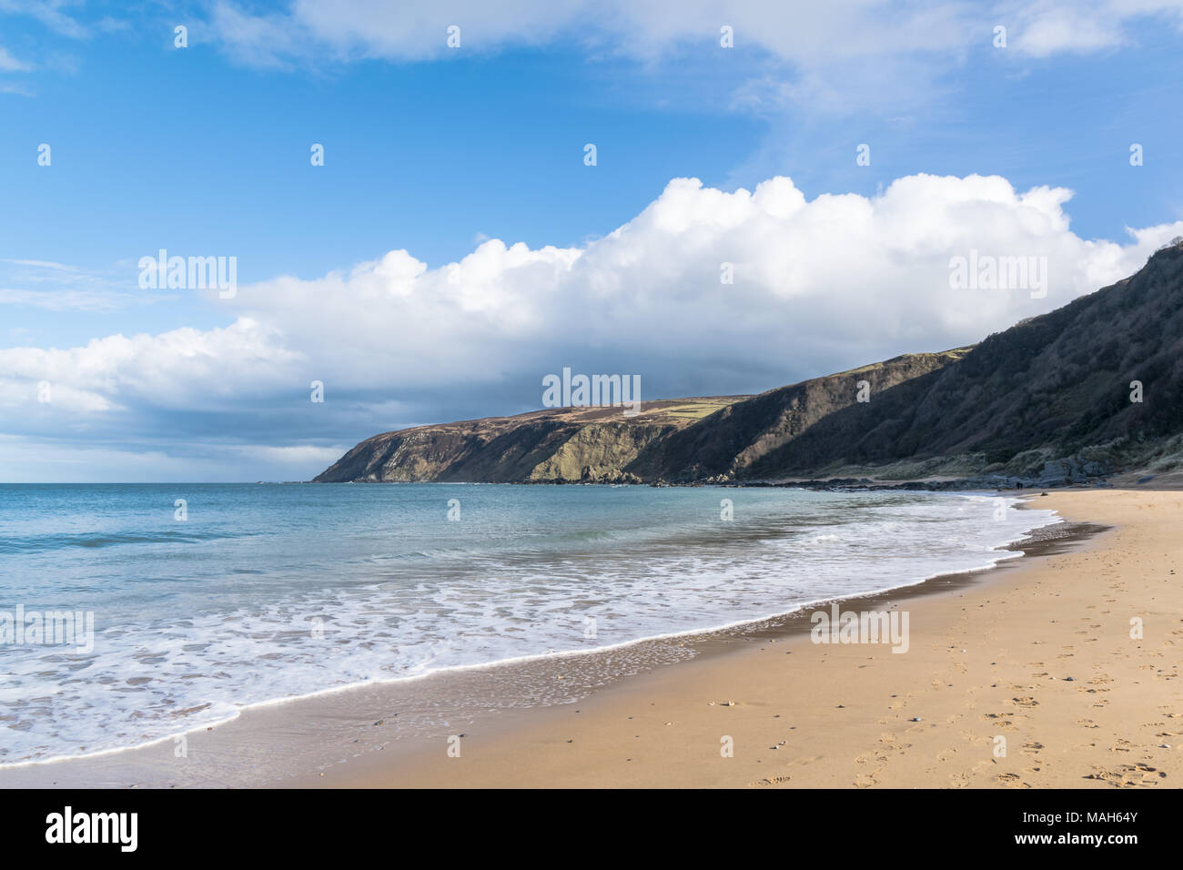 White sandy beach in Ireland with turquoise water and blue sky. This is Kinnagoe Bay in Donegal Ireland - Stock Image
