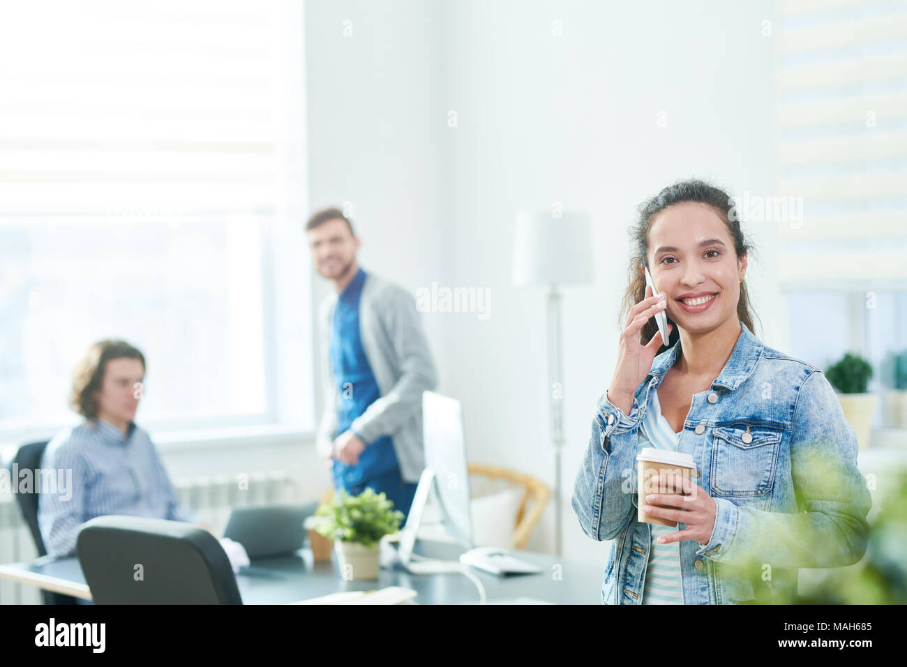 Excited modern office manager talking on phone friendly - Stock Image