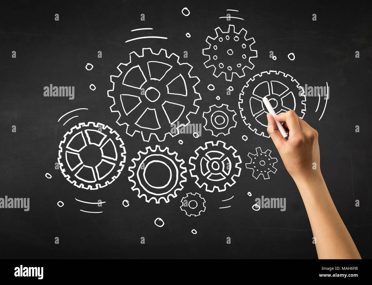 Female hand holding white chalk in front of a blackboard with gears drawn on it Stock Photo