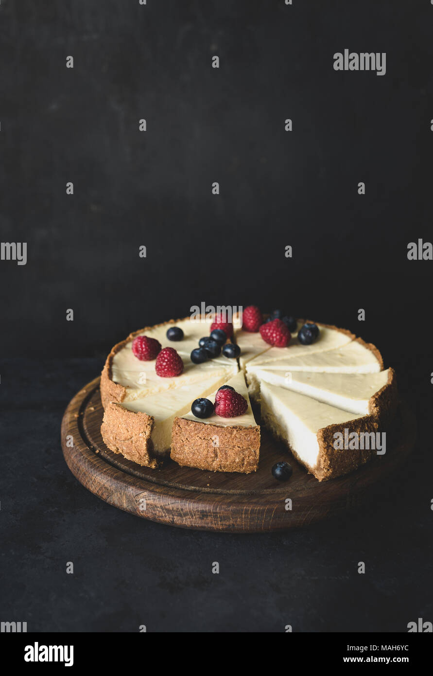 Cheesecake with fresh berries on cutting board on dark background. Selective focus, toned image. Copy space for text. - Stock Image