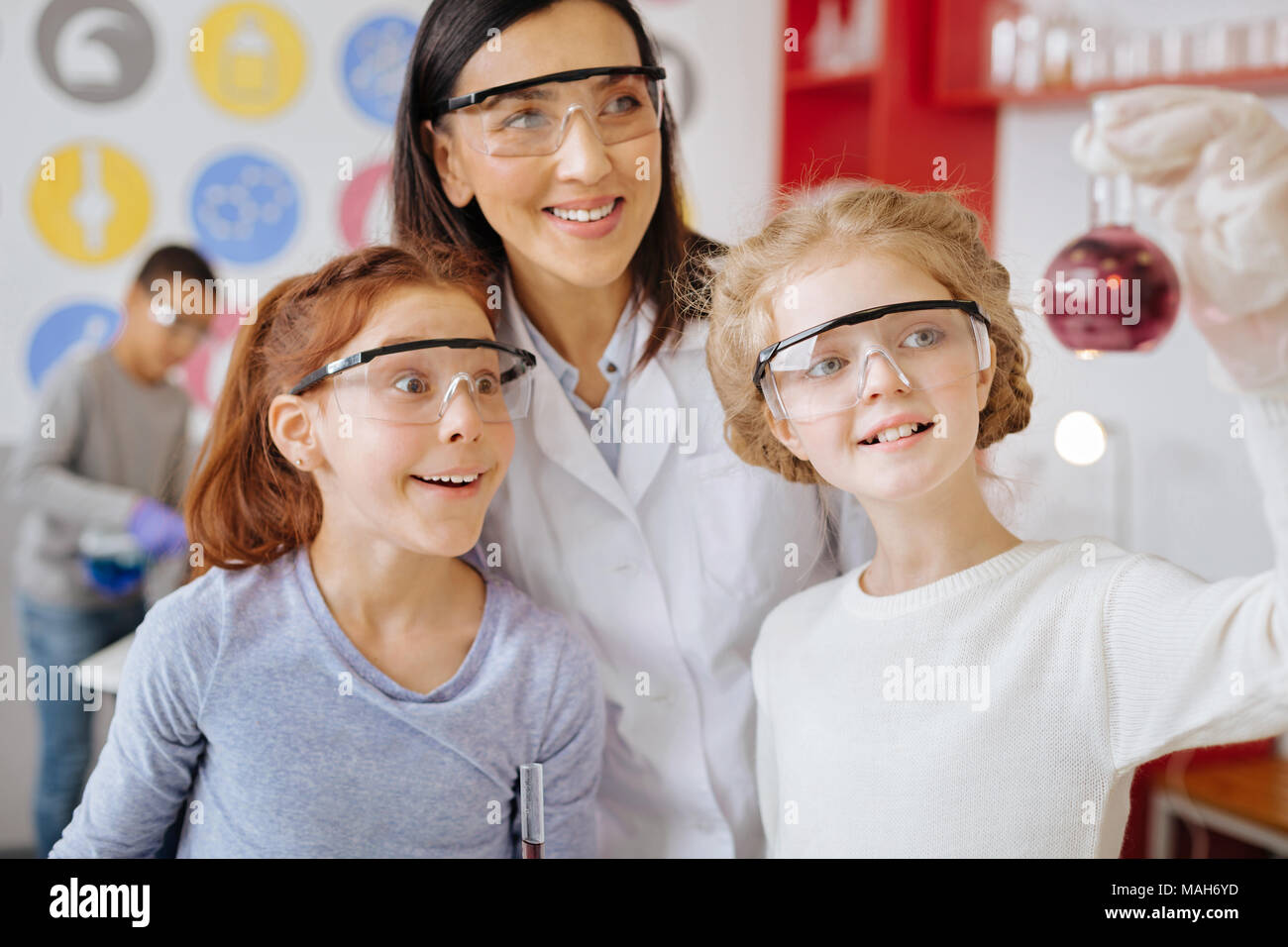 Cheerful students and teacher checking for sediment in flask - Stock Image