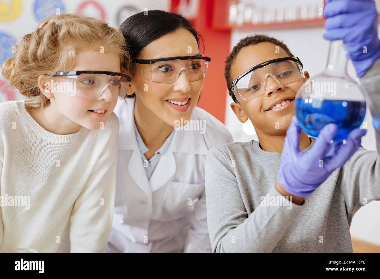 Schoolboy showing flask with substance proudly to teacher and classmate Stock Photo