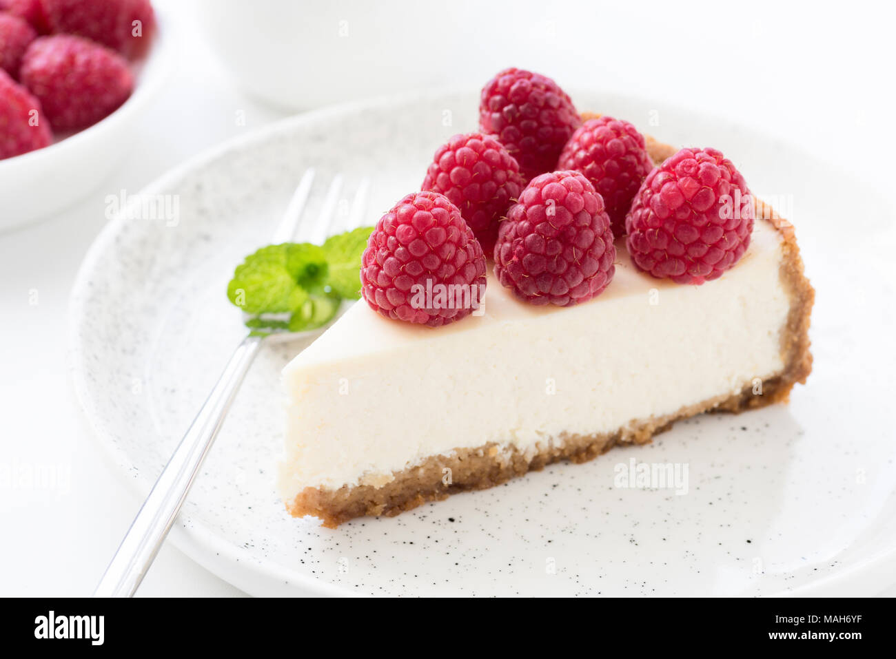 Cheesecake with fresh raspberries on white plate. Closeup view, selective focus - Stock Image