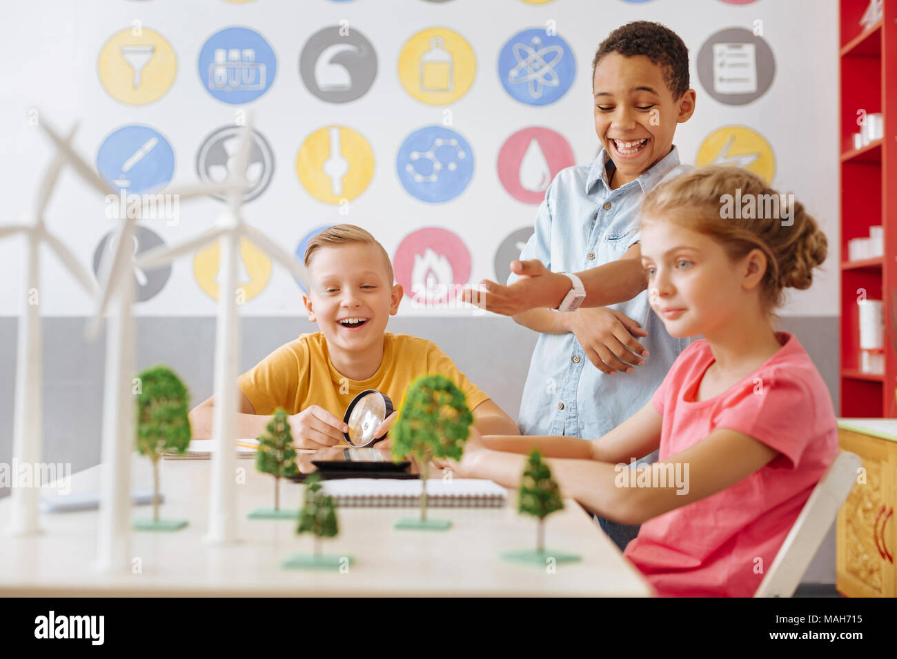 Upbeat classmates joking while discussing eco-project - Stock Image