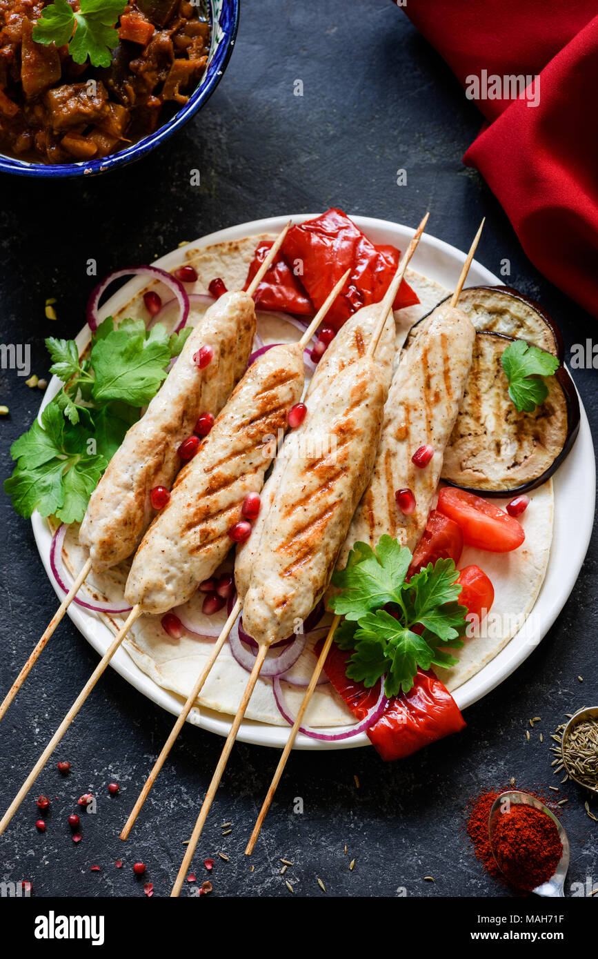 Arabic Chicken kebab, Adana kebab or sish kebab served with grilled pepper, eggplant, parsley and onion. Top view, selective focus Stock Photo