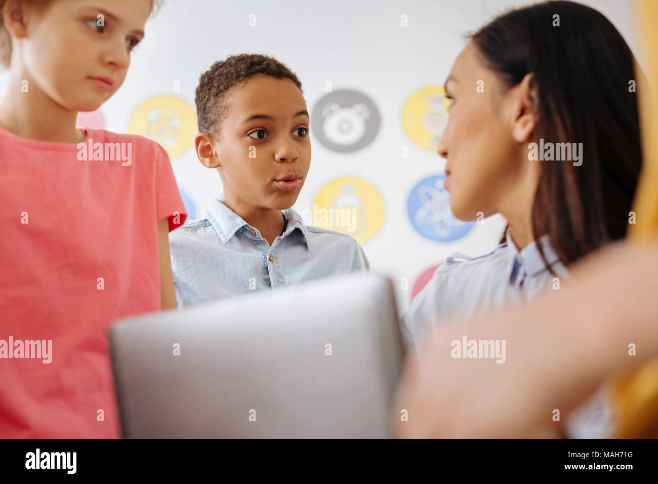 Cute boy communicating with his teacher after class - Stock Image