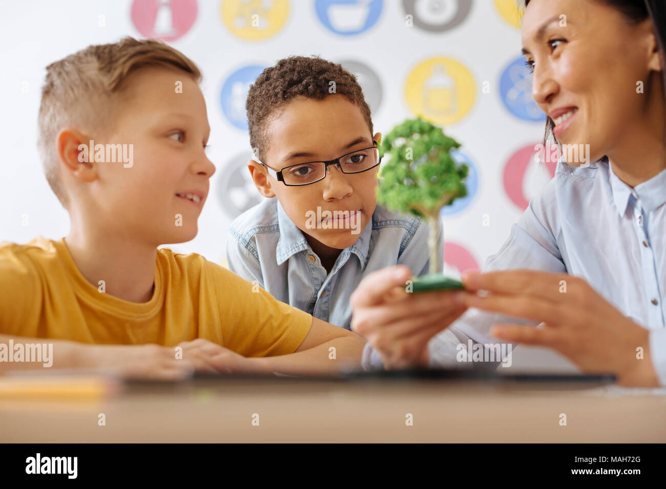 Cheerful teacher showing tree model to her students - Stock Image