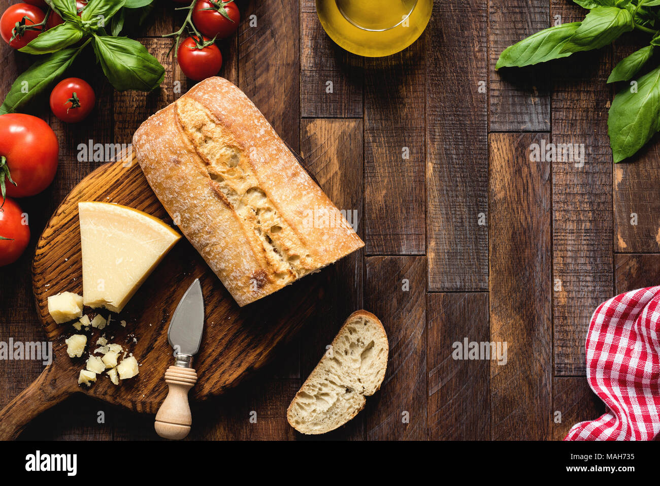 Italian food on rustic wood background, top view. Parmesan cheese, ciabatta, bruschetta, basil, olive oil and tomatoes. Italian cuisine - Stock Image