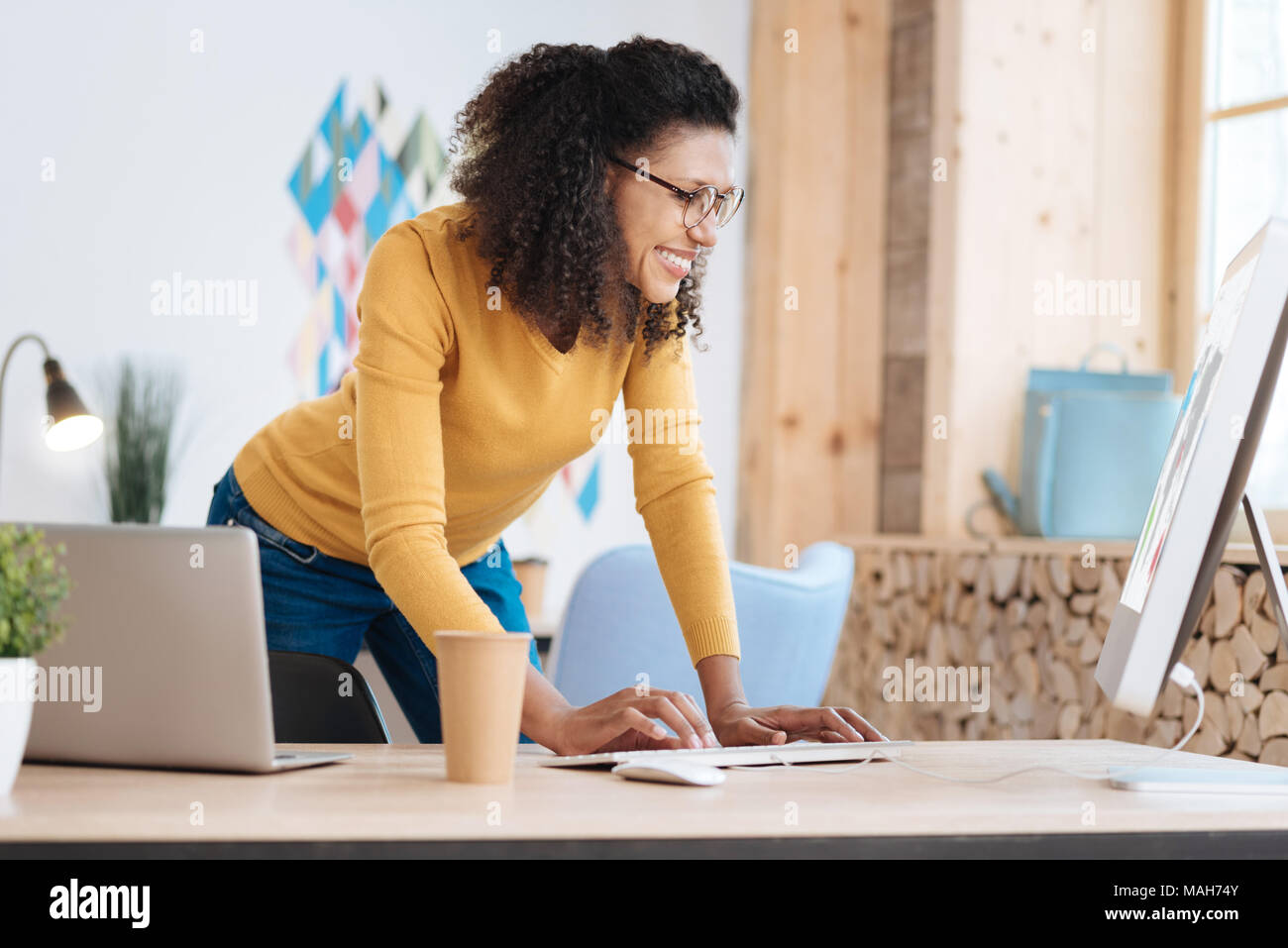 Joyful woman working on her project - Stock Image
