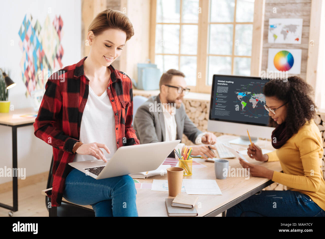 Content woman working in office with her co-workers - Stock Image
