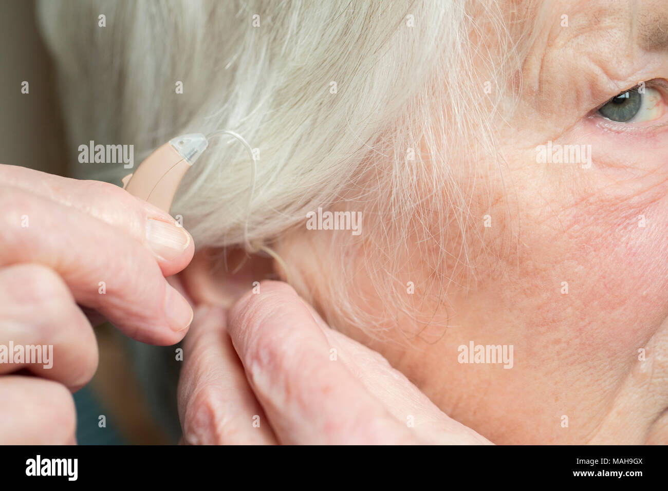 Close Up Of Senior Woman Putting In Hearing Aid - Stock Image