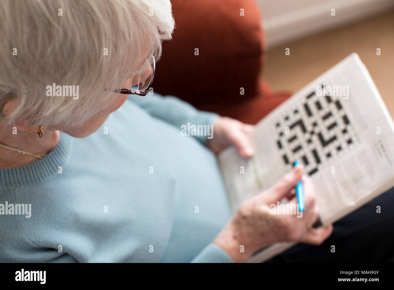 Senior Woman Doing Crossword Puzzle At Home - Stock Image