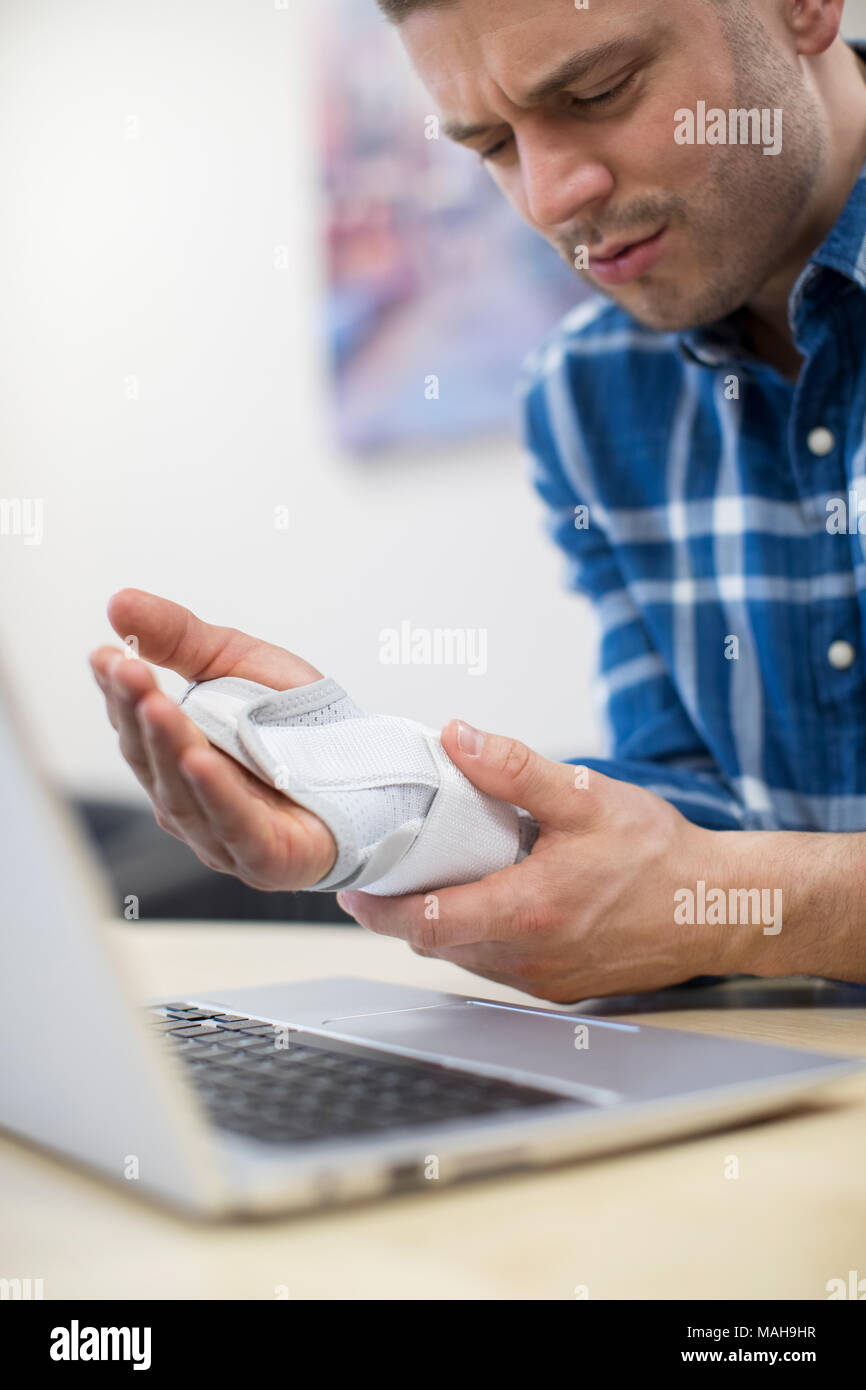 Businessman Using Laptop Suffering From Repetitive Strain Injury (RSI) - Stock Image