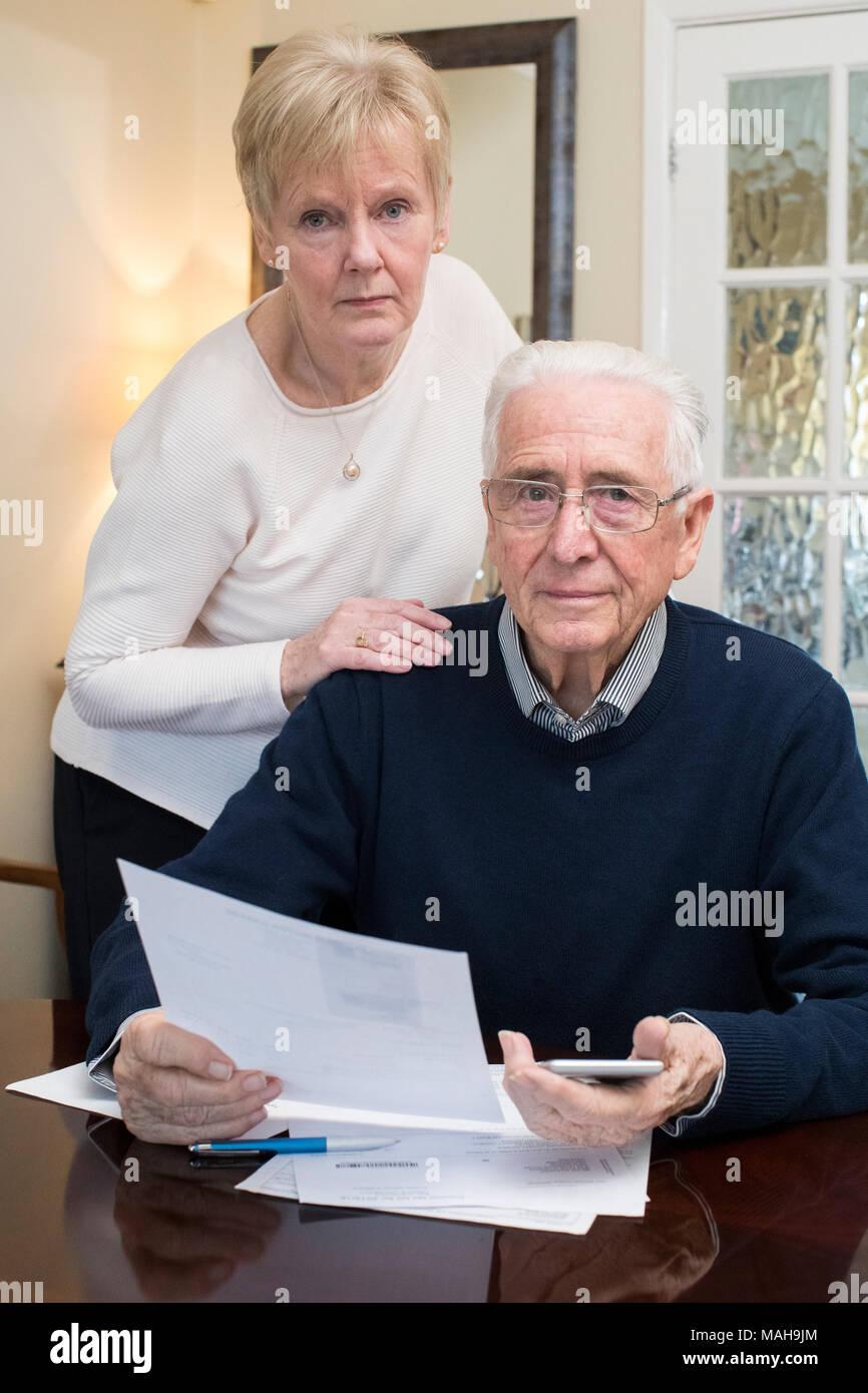 Portrait Of Concerned Senior Couple Reviewing Domestic Finances - Stock Image