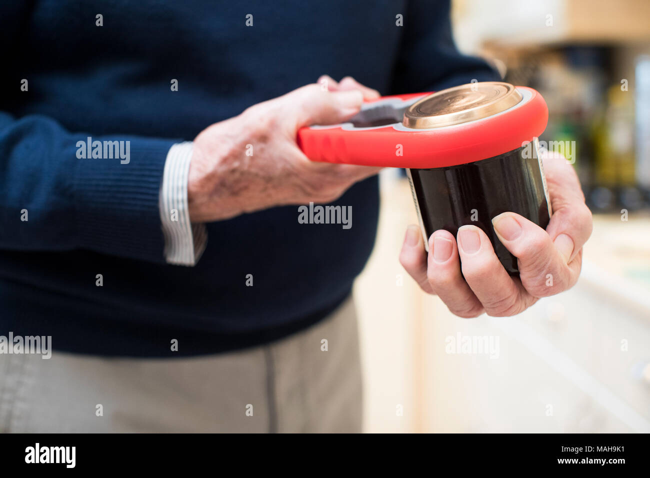 Close Up Of Senior Man Taking Lid Off Jar With Kitchen Aid - Stock Image