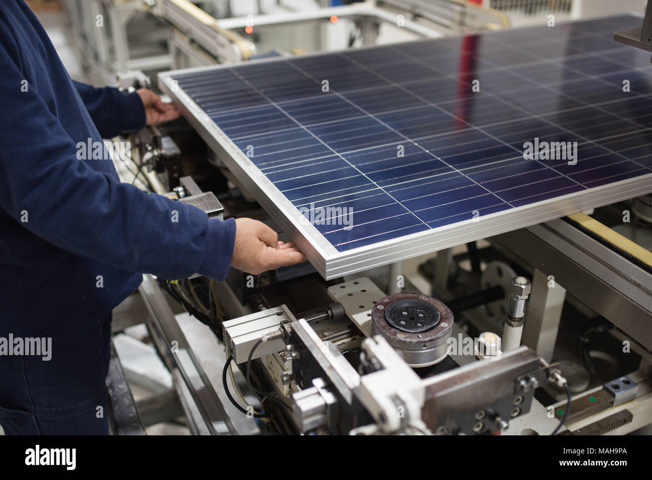 production of solar panels, man working in factory - Stock Image