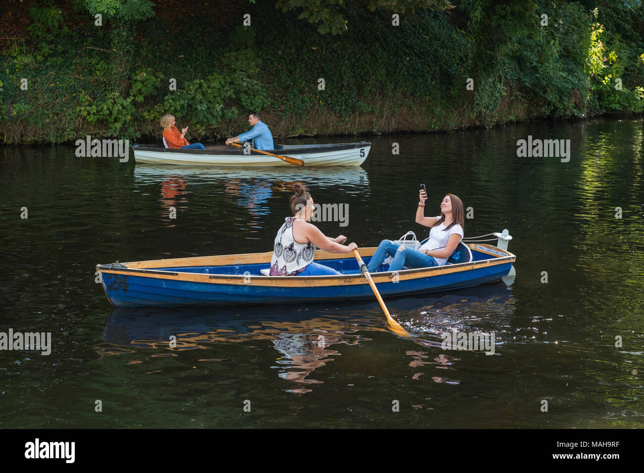 4 people boating, relaxing & having fun in 2 rowing boats (1 young woman in boat is taking selfie) - River Nidd in summer, Knaresborough, England, UK. - Stock Image