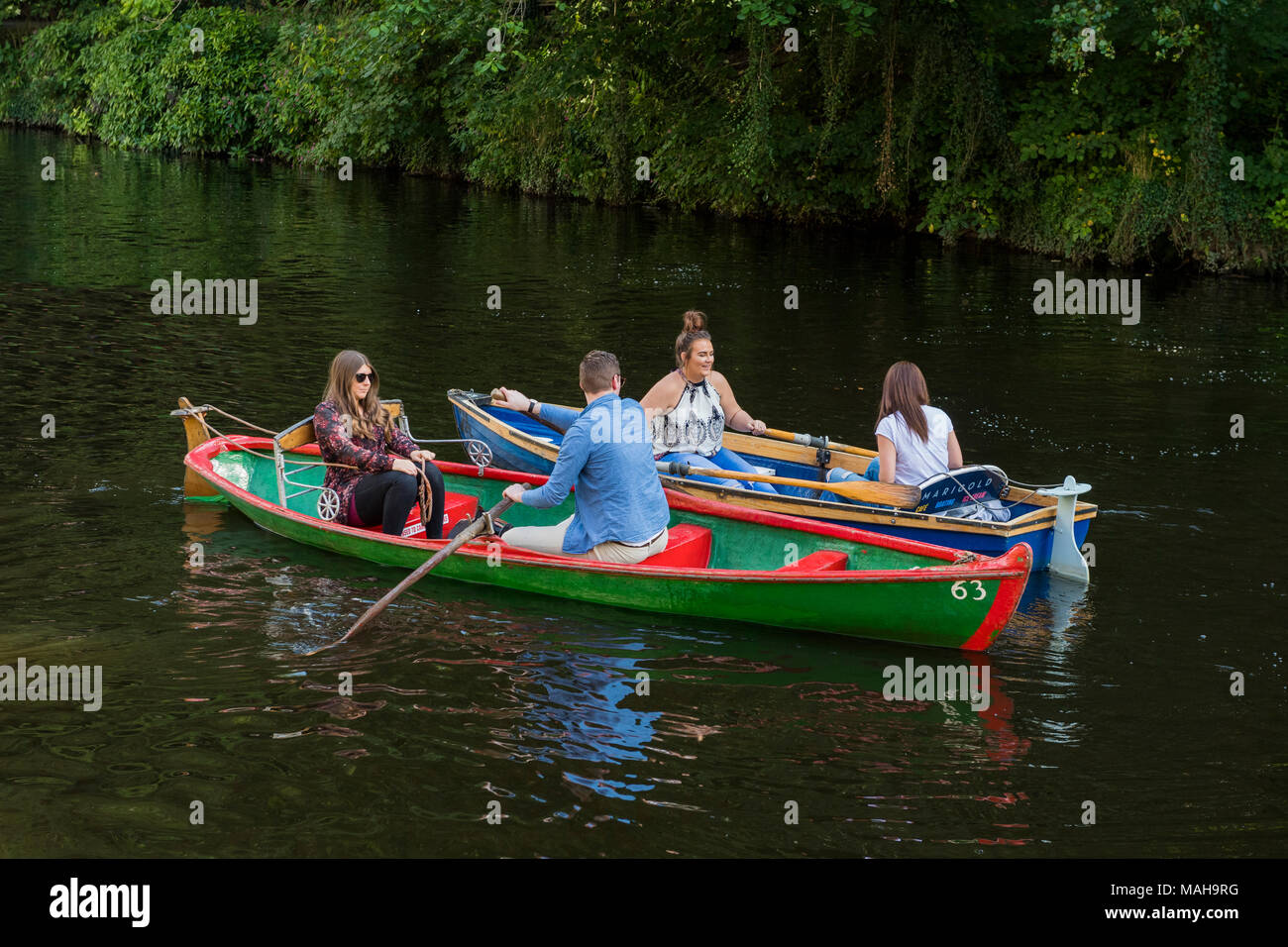 4 people boating in pairs, relaxing & having fun in 2 rowing boats side by side & about to collide - River Nidd in summer, Knaresborough, England, UK. - Stock Image