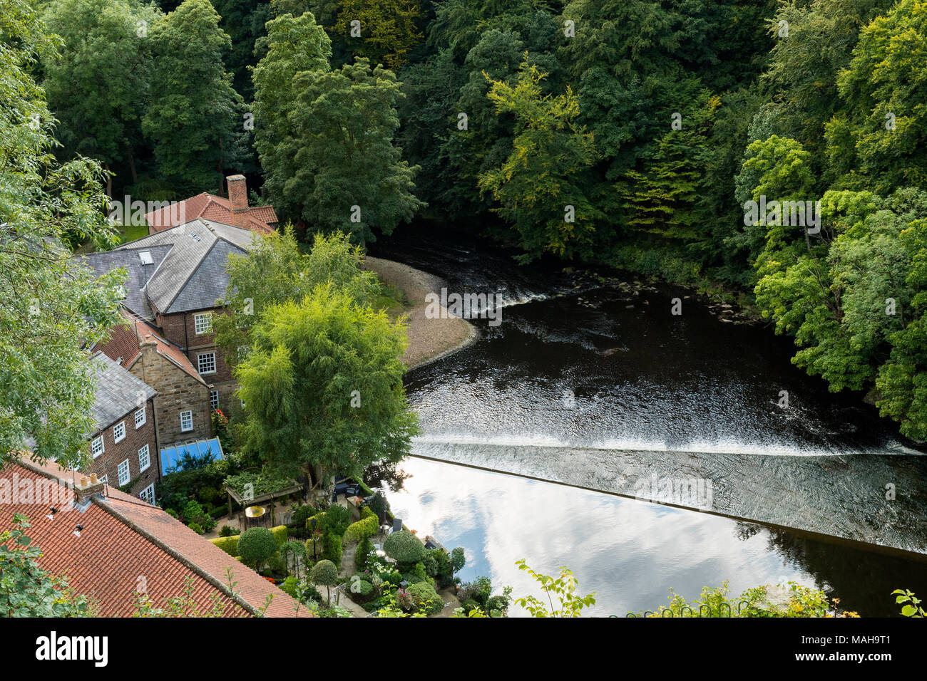 High view of water flowing over weir across River Nidd & historic Castle Mills, an old textile mill converted to homes - Knaresborough, England, UK. - Stock Image