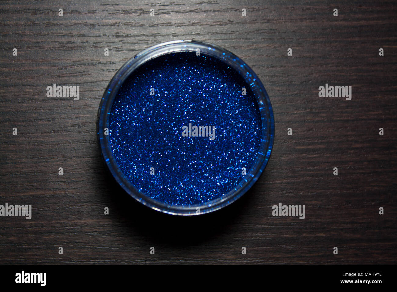 Cobalt blue glitter powder isolated on dark wooden background from a high angle view - Stock Image